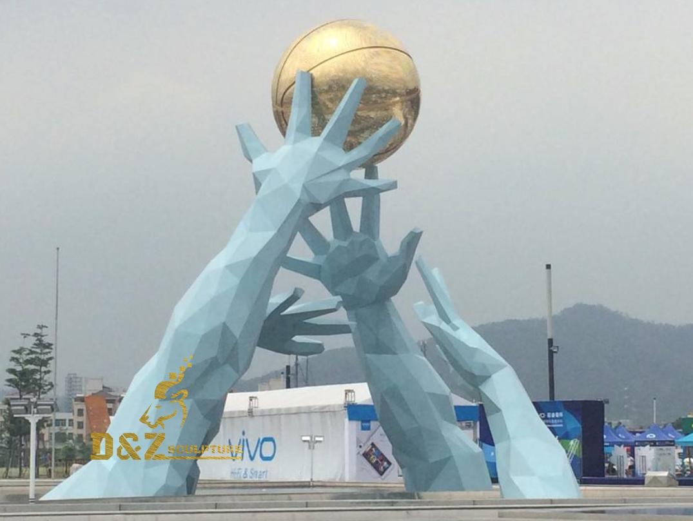 Hand holding a ball sculpture
